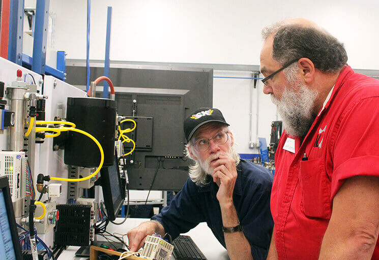 Joseph LeDuc of Chippewa Falls, left, listens as CVTC Industrial Mechanic instructor Jeff Johnson explains procedures on an electrical switch system tied into a computer at the Industrial Mechanic Academy at CVTC Aug. 11.