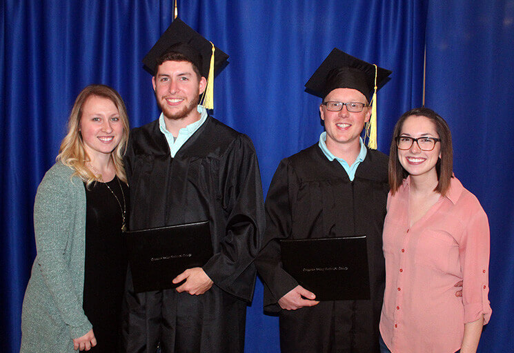 From left, Amanda and Guy Hudson, and Lucas and Kayla Bleskacek gather after the CVTC River Falls campus commencement ceremony Thursday, May 18. Guy and Lucas became good friends both needing a change of careers and entered the Residential Construction program together. Their wives became good friends as well.