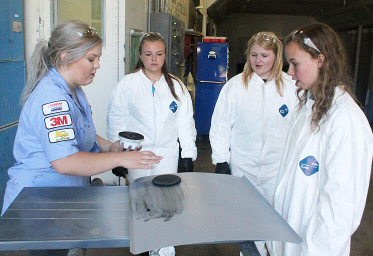 From left, CVTC Auto Collision Repair and Refinish program student Leann Rafferty of Lublin demonstrates a sanding technique to high school students Aliyah Loofboro of Colfax, and Hope Bander and Kate Gadient of Pepin during a one-day camp June 23 in which girls could explore the male-dominated field. Each of the camp attendees repaired a dent, smo