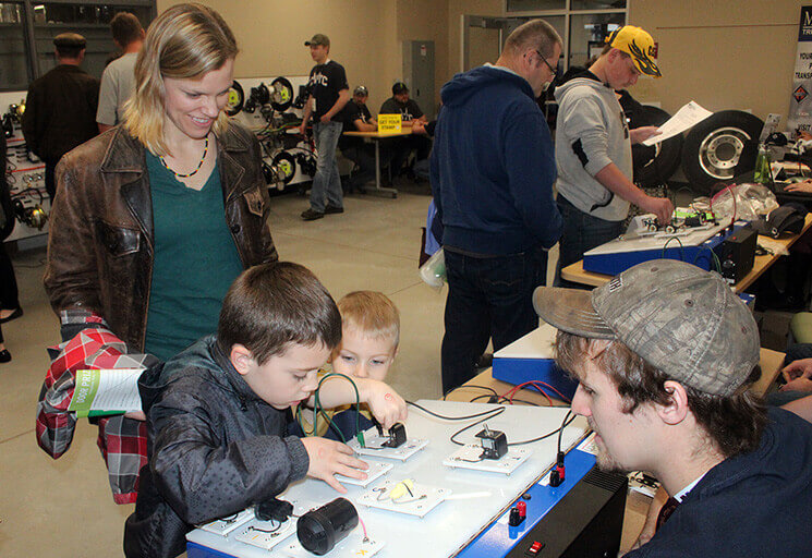 Gunnar, left, and Jamison Henke play with a test board that demonstrates the circuits used in the lighting systems on trucks while their mother, Christina, looks on at the CVTC Energy Open House Thursday, April 20. CVTC student Preston Miller of Menomonie, right, first showed the boys how to make the lights work.