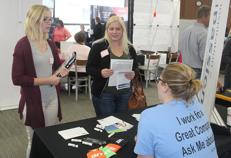 CVTC Human Resources program students Brooke Carrigan of Stanley, left, and Shioban Smith of Bloomer talk with Emily Balfanz of Logistics Health Inc. of La Crosse at the Fall Career Fair at CVTC's Business Education Center in Eau Claire Oct. 18.