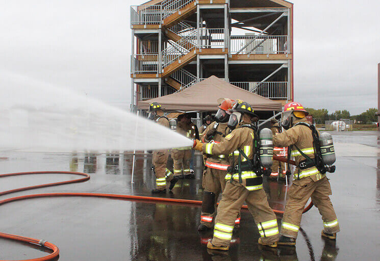 "Firefighters from the Owen-Withee-Curtis and Altoona districts control a fire hose with the help of Altoona firefighters at the CVTC firefighter training area in Eau Claire Saturday, Oct. 9 as firefighters from 15 departments practiced for an upcoming state certification test. In the background is the multi-use three-story ""splash tower"" built this"