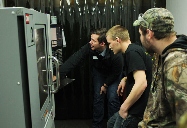 CVTC instructor Andrew Kott, left, demonstrates equipment in the CVTC Mobile Manufacturing Lab during the Manufacturing Show in March. Thanks to a new National Science Foundation grant, the lab will soon include a small-scale simulation of an automated distribution center and will also be coming the Durand and Menomonie school districts while maint