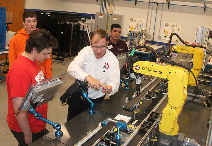 CVTC Industrial Mechanic Instructor Tim Tewalt, center shows students a USB flash drive produced by the simulated manufacturing center, new this year as CVTC opens its 2017-18 academic year. Students from left are Brandon Engevold of Whitehall (rear), Deven Risler of Altoona and Carlos Anes of Eau Claire.