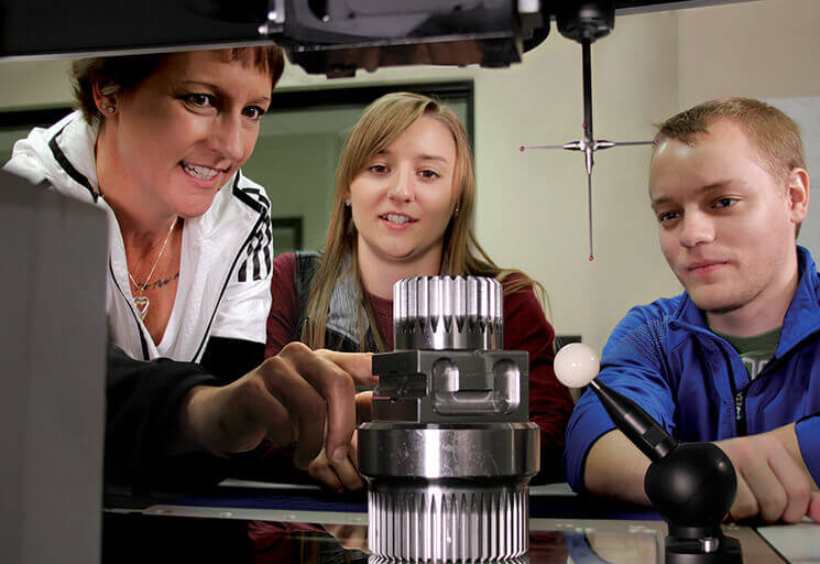 Phillips Medisize quality team members Wendy Martin and her children Ali and Brady Siler examine a Zeiss O-Inspect system at the CVTC Manufacturing Education Center. The family members were all enrolled in the Manufacturing Quality program at CVTC this fall.