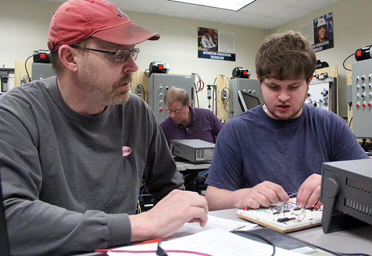 John Swanson of Prescott, left, and Bert Graham of Roberts work together testing the logic gates on an electronic bread board at an Automation Engineering Technology lab at the CVTC River Falls campus. The first manufacturing program offered at the campus is finishing its first academic year this spring.