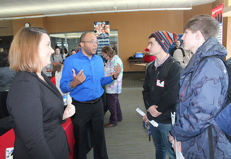CVTC Business management students Trevor Hurt of Mondovi, right, and Scott Carey of Eau Claire speak with US Bank representatives Sara Hefty and Jeff Webb at the CVTC Spring Career Fair March 8.