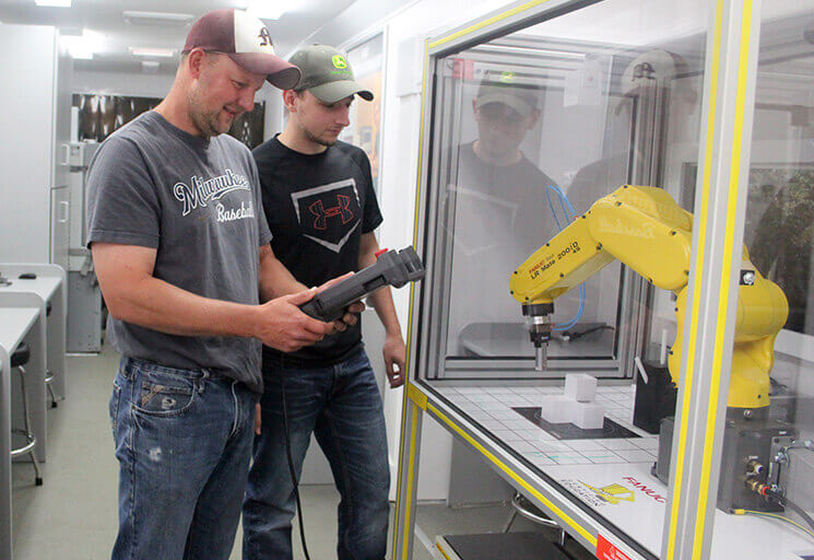 Menomonie High School technical education teachers Ryan Sterry, left, and Ben Edelburg work with the Fanuc Robotic Arm inside the CVTC Mobile Manufacturing Lab parked outside the CVTC Business Education Center in Eau Claire Tuesday, July 25. The mobile lab will be coming to Menomonie in November.