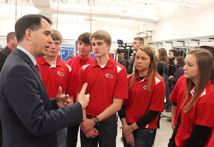 Gov. Scott Walker speaks with a group of Eleva-Strum High School students following his remarks on his proposed state budget at CVTC's Applied Technology Center Friday, Feb. 10.