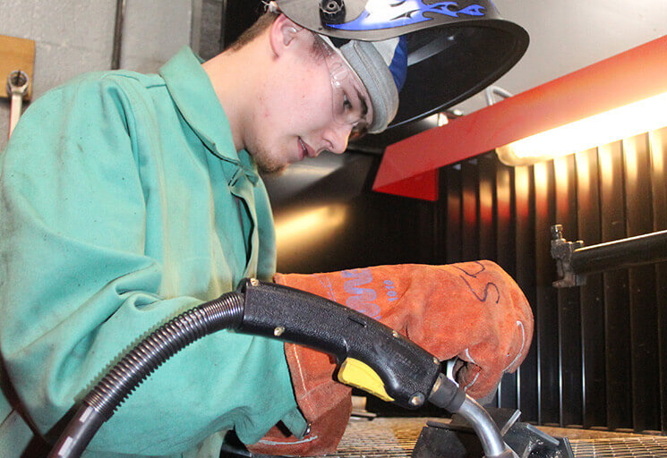 Cadott High School student Derek Scheidler sets up in a welding booth at the high school Feb. 20 during a Welding Academy class.