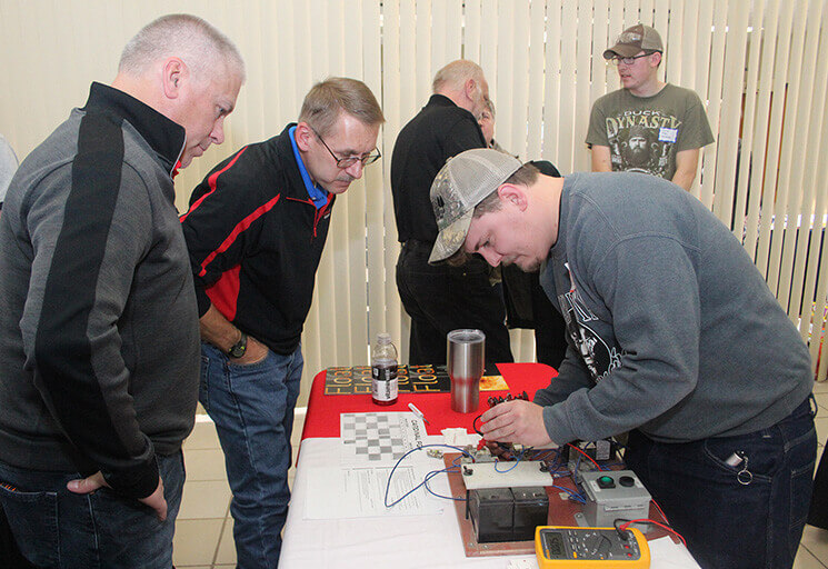 CVTC Automation Engineering Technology student Lucas Gont of Chippewa Falls troubleshoots a circuit at the Cardinal FG table at the CVTC Fall Career Fair Wednesday, Oct. 24. Looking on from left are Kevin Nolan and Scott Brunner from the company's Menomonie plant. Cardinal FG is seeking students and graduates from Gont's program.
