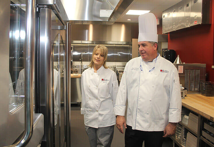 CVTC Culinary Management instructor Kevin Brown shows a rotating deck oven while giving a tour of the new state-of-the-art teaching kitchen. At left is new program student Judy Ewer, a Gilman native and former Lake Holcombe resident.