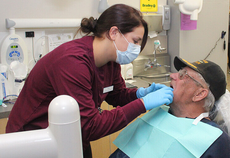 Ciara Smith, a CVTC Dental Hygienist student from Arcadia, checks out an infected tool that U.S. Army veteran David Franzwa of Mondovi came to have extracted at the Give Vets a Smile Day event at the CVTC Dental Clinic Saturday, Nov. 3. This year, the event featured an expanded list of free services for vets, from additional health services to haircuts and chair massages.