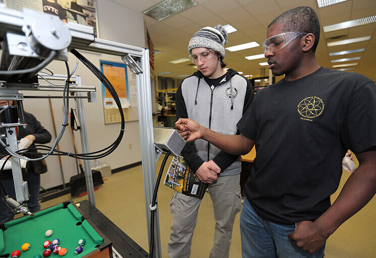 CVTC Automation Engineering Technology student Soren Sigurdsen, right, shows Eau Claire Regis High School senior Declan Dooley how to operate an automated miniature billiards game at the CVTC Manufacturing Show March 1.