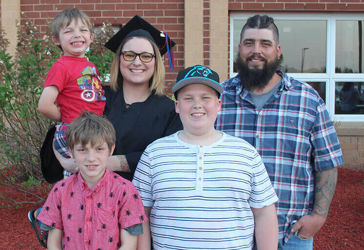 CVTC graduate Melanie Carey holds her son, Xander, 6, who was born just four days before she started in the Nursing program. Her husband, Jeff, and their other sons Reider (left) and Chris joined mom