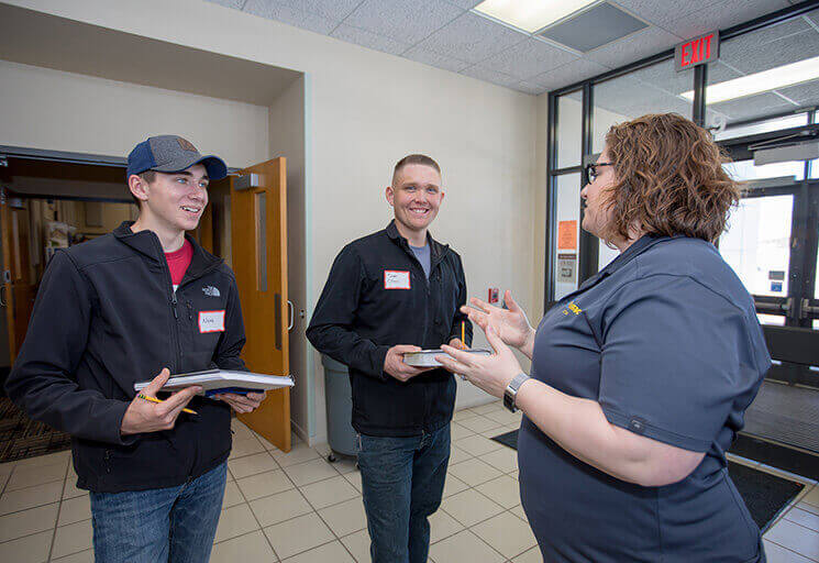 CVTC Welding students Noah Keck of Baldwin, left, and Sam Olson of Eau Claire talk with Katelyn Gollberg, HR administrator for USEMCO Inc., a sanitary equipment manufacturer from Tomah, at the CVTC Spring Career Fair March 7.