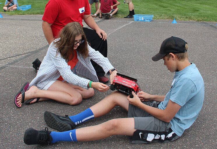 CVTC STEM Race Camp participants, from left, Hunter Moritz of Menomonie, Rebecca Hansen of Brooklyn Center, Minn., and Evan Eslinger of Chippewa Falls, work together to make adjustments to their car in preparation for the final races, at the CVTC Manufacturing Education Center June 21.