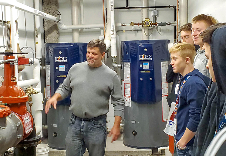 Russell Boos, a journeyman steamfitter from Mondovi, shows a group of area high schools students a side of the Pablo Center that few people see. During Apprenticeship Exploration Day, Boos took them to rooms containing the inner electric, plumbing, heating and ventilation infrastructure and talked about the role of the skilled trades in building the center.
