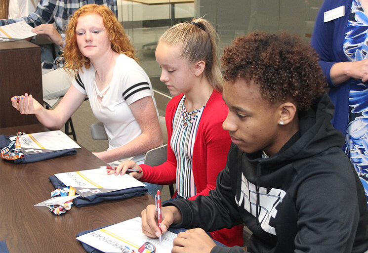 North High School freshmen, from left, Janaya Goldbach, Alaina Halvorsen and Averyon Sands sign their commitments to the Business Management Associate Degree Academy at CVTC Wednesday, September 18. Students who complete the program will graduate from high school with both a high school diploma and an associate degree from CVTC.
