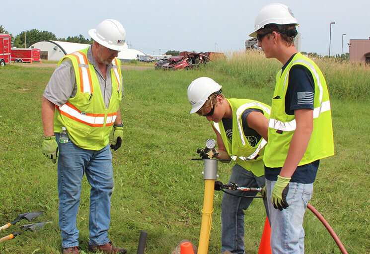 CVTC Gas Utility Construction & Service program students Tyler Bee of Elmwood, center, and Den Henning of Eau Claire test a pressurized line for leaks while instructor RC Jensen, left, looks on, at the CVTC West Campus this summer. For training purposes, the line was pressurized with air, not natural gas.