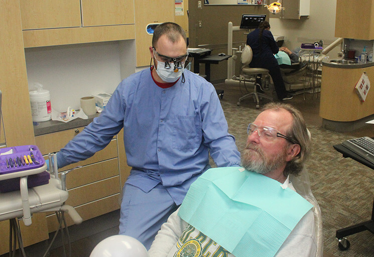 Matt Rindahl, a dental hygienist with the Houston Dental Clinic in Tomah, prepares to help Army veteran Steve Prince of Chippewa Falls at the Give Vets a Smile Day event at the CVTC Dental Clinic Nov. 2. Rindahl, a 2016 CVTC Dental Hygienist program graduate is a Navy veteran.