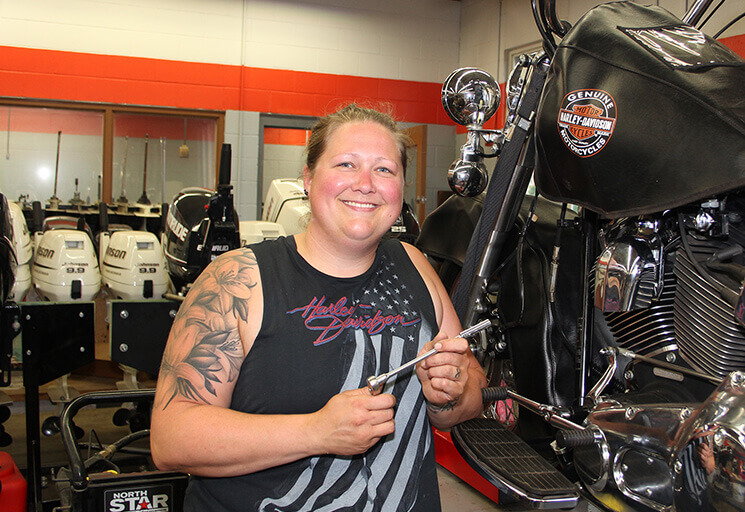 Portia Maves poses with a Harley-Davidson motorcycle she worked on at the CVTC Marine, Motorcycle and Outdoor Power Products Technician program lab. After surviving breast cancer, Maves decided to pursue a lifelong dream to become a motorcycle mechanic. She was one of seven graduates on the program honored at the CVTC Summer Commencement Thursday, Aug. 1.