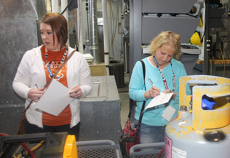 Two women look for safety hazards set up in the HVAC lab at CVTC's Energy Education Center during a Hazard Hunt as part of the 2019 Safety Day.