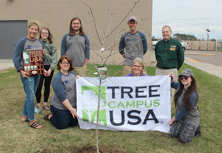 CVTC Horticulture Club members pose with the Tree Campus USA banner by a newly planted tree at the Energy Education Center. Standing at right is Brad Johnson, urban forestry coordinator for the DNR's western district.