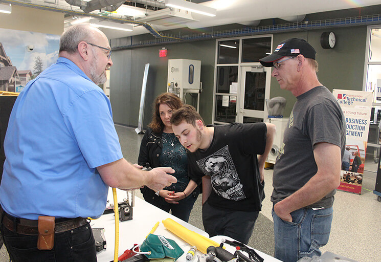 CVTC Gas Utility Construction & Service instructor RC Jensen, left, shows a tool used in the trade to incoming program student Michael Carolfi of Wisconsin Rapids while Michael's parents, Berni and Dave, look on at the CVTC West Campus Open House Thursday, April 25.