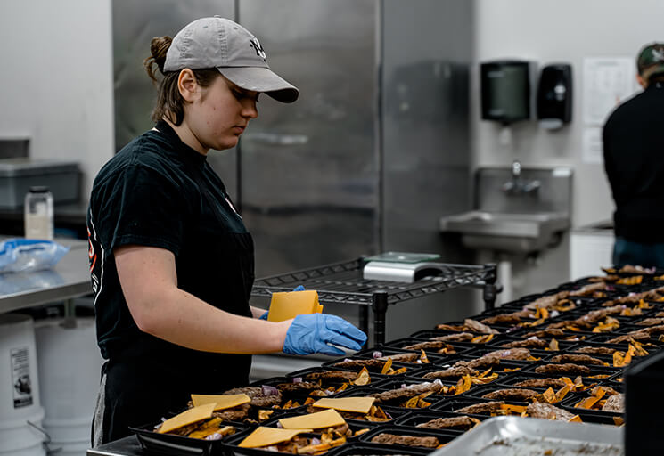 A worker prepares meals at the Midwest Meals facility in Eau Claire. CVTC Culinary Management students will be completing their kitchen work at home using materials assembled by the company, including packaging like those shown here.