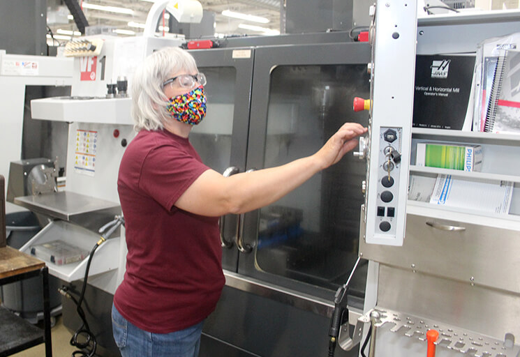 Deb Van Den Heuvel programs a CNC machine in the CVTC Machine Tooling Technics lab during one of her final weeks in the program before graduating. Students working in labs are required to wear masks and maintain social distancing to the extent possible.