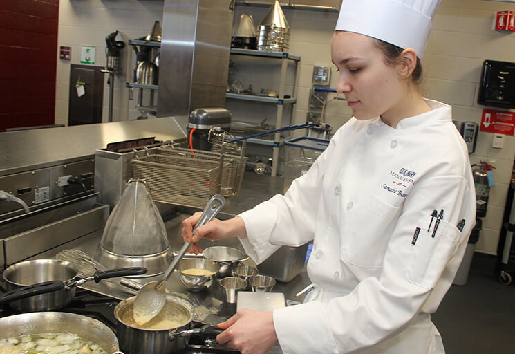 CVTC Culinary Management student Samantha Bauer of Eau Claire stirs a roux that was to become an ingredient in a soup in the CVTC culinary kitchen. Bauer is one of the students excited about a program partnership with Midwest Meals that could earn her a scholarship.