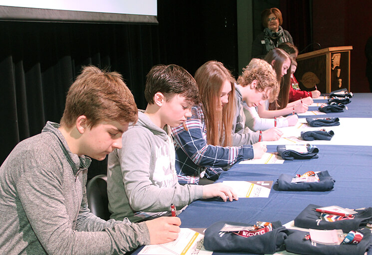 Menomonie eighth graders sign agreements to take part in the Business Management Associate Degree Academy as high school freshmen next year at a signing day ceremony March 11. By completing the program over four years, the students can earn an associate degree when they graduate from high school.