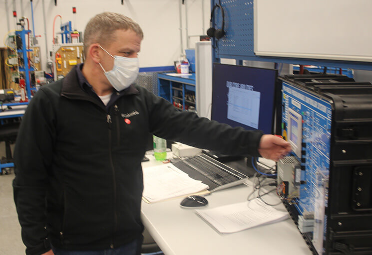 Curtiss Anderson, a technical operations manager at Premium Waters in Chippewa Falls, works on an electrical controller training unit in the Mechatronics lab at CVTC in December.